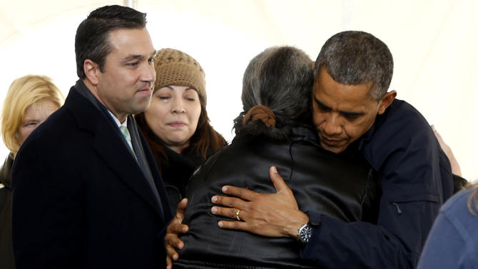 President Barack Obama hugs a woman as he visits the FEMA recovery center on the grounds of New Dorp High School, Thursday, Nov. 15, 2012  on Staten Island, in New York. At left is Rep. Michael Grimm, R-N.Y. (AP Photo/Carolyn Kaster)