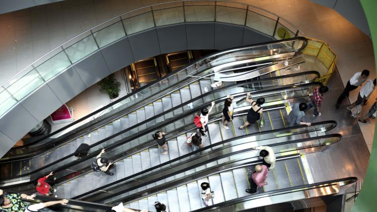 FILE - In this Feb. 17, 2009 file photo, shoppers travel up and down the escalators at a shopping mall in Singapore. Already one of the most densely populated countries in the world, tiny land scarce Singapore is projecting its population to swell by a third over the next two decades. To accommodate the influx, its planners envisage expanding upward, outward and downward. The population target of 6.9 million people, an increase of 1.3 million from the present, is contentious in a country where rapid immigration has already strained services such as public transport and contributed to a widening wealth gap. (AP Photo/Wong Maye-E, File)