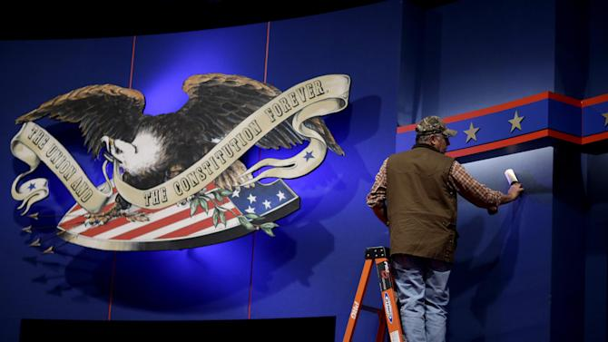 A worker cleans lint off the background of the stage for a debate at the University of Denver ,Tuesday, Oct. 2, 2012, in Denver. President Barack Obama and Republican presidential candidate and former Massachusetts Gov. Mitt Romney will hold their first debate Wednesday. (AP Photo/David Goldman)
