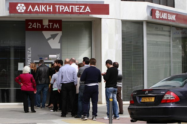 People queue to use the ATM of a closed branch of Laiki Bank in capital Nicosia, Thursday, March 21, 2013. The European Central Bank says it will keep emergency aid for Cyprus' troubled banks in place