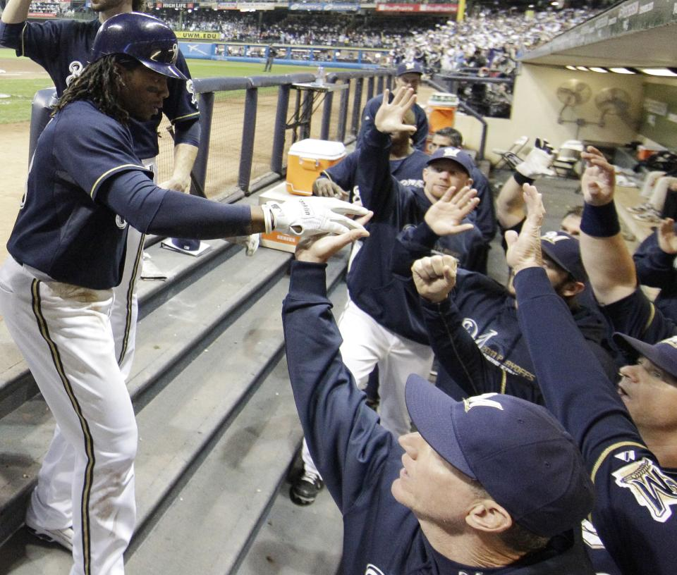 Milwaukee Brewers' Rickie Weeks is congratulated in the dugout after hitting a two-run home run during the fourth inning of Game 2 of baseball's National League championship series against the St. Louis Cardinals Monday, Oct. 10, 2011, in Milwaukee. (AP Photo/David J. Phillip)