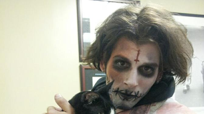 In this undated photo provided by BluePearl Veterinary Partners, Jeremy Zelkowitz, who dresses in character as a zombie for a year-round haunted house in Times Square, holds a cat named Disaster which he found crossing 42nd Street in Manhattan on March 30, 2013. (AP Photo/BluePearl Veterinary Partners)