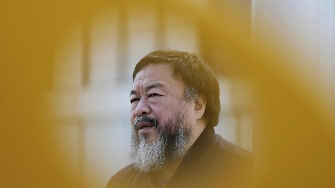 FILE - In this March, 2015, file photo, dissident Chinese artist Ai Weiwei speaks during an interview near a playground outside a shopping mall in Beijing. The British Embassy in Beijing has restricted a visa for dissident artist Ai Weiwei, alleging he failed to declare that he had a criminal conviction, a claim that his lawyer disputed on Thursday, July 30, 2015. (AP Photo/Andy Wong, File)