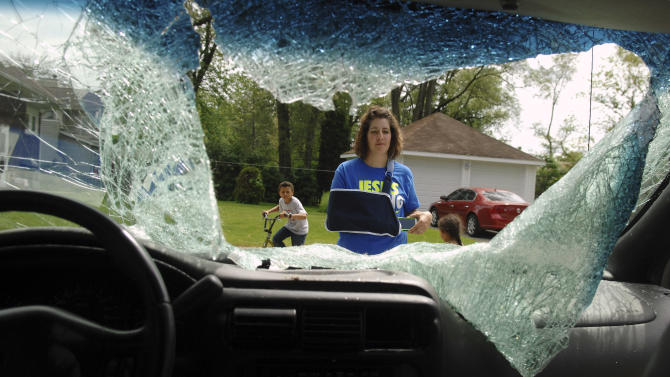 In this Tuesday, May 27, 2014, photo, Heidi Conner, of West Dundee, Ill., describes how a 200 pound deer leapt from an overpass and landed on her minivan as she and her four children traveled along an Illinois interstate on Sunday, May 25. Conner says the accident totaled the van and caused minor injuries. (AP Photo/Daily Herald, Rick West) MANDATORY CREDIT, MAGS OUT