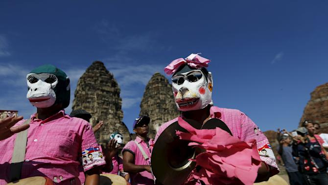People wears masks of monkeys at the Pra Prang Sam Yot temple before the annual Monkey Buffet Festival in Lopburi