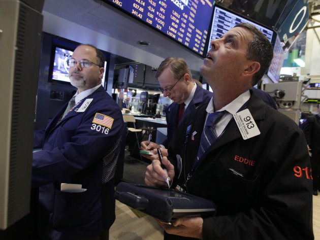 Trader Edward Baumann, right, works on the floor of the New York Stock Exchange Wednesday, June 20, 2012. Stocks edged lower early Wednesday after investors saw signs that economies could be slowing d