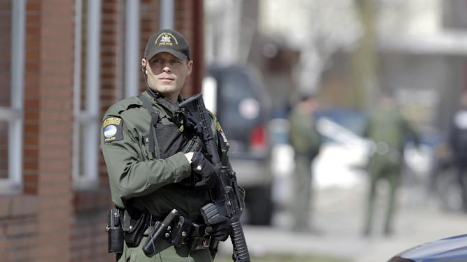 A law enforcement officer stands on Main Street in Herkimer, N.Y., during the search for a suspect in two shootings that killed four and injured at least  two on, Wednesday, March 13, 2013. Authorities were looking for 64-year-old Kurt Meyers, said Herkimer Police Chief Joseph Malone. Officials say guns and ammunition were found inside his Mohawk apartment after emergency crews were sent to a fire there Wednesday morning.  (AP Photo/Mike Groll)
