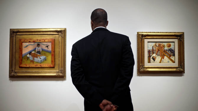 """This Feb. 8, 2013 photo shows Rory Hall, of Atlanta, viewing two paintings by artist Frida Kahlo as part of the exhibition """"Frida & Diego: Passion Politics and Painting,"""" featuring the works of Kahlo and Diego Rivera at the High Museum in Atlanta. The exhibit features more than 140 works, making it the largest exhibition of the couple's art ever displayed together. Atlanta's High will be the only U.S. venue for the exhibition, which opens Feb. 14 and runs through May 12. (AP Photo/David Goldman)"""