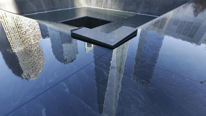The One World Trade Center building, center, is reflected on one of the pools at the 9/11 Memorial, in New York, Monday, March 23, 2015. The first stair-climb benefit will be held at One World Trade Center in May to raise money for military veterans, two foundations, the Stephen Siller Tunnel to Towers Foundation and the Captain Billy Burke Foundation, formed after the 9/11 attacks announced Monday. (AP Photo/Richard Drew)