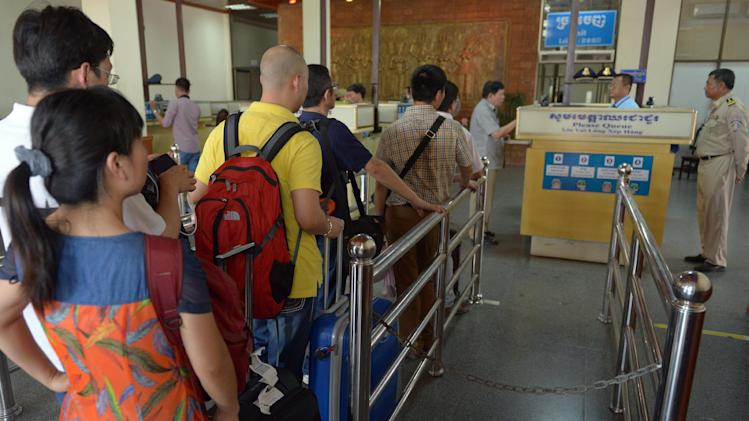 Chinese tourists (R) queue at the immigration check point after arriving in Cambodia on May 16, 2014
