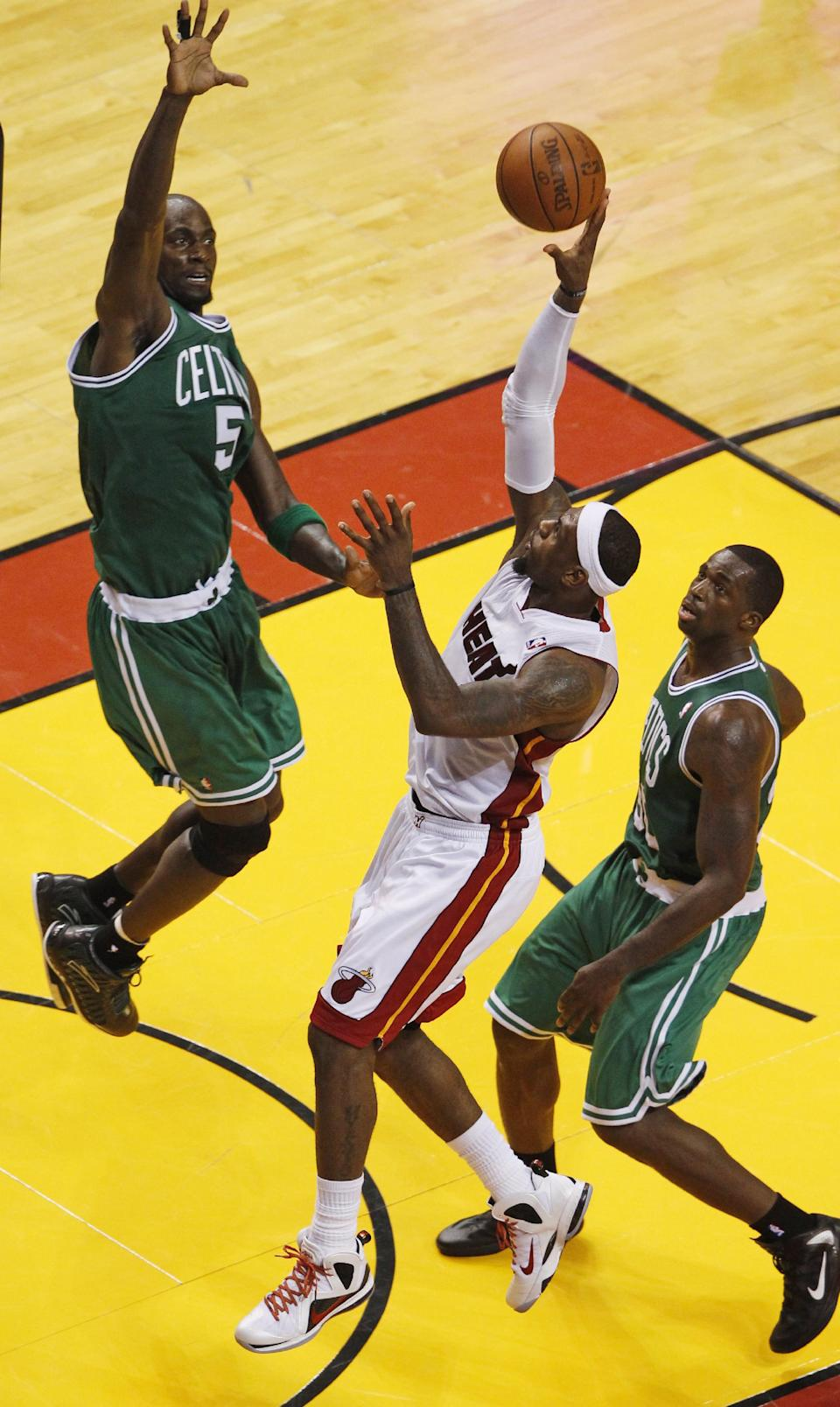 Miami Heat's LeBron James (6) drives to the basket as Boston Celtics' Kevin Garnett (5) defends during the second half of Game 7 of the NBA basketball playoffs Eastern Conference finals, Saturday, June 9, 2012, in Miami. At right is Celtics' Brandon Bass (30). (AP Photo/Wilfredo Lee)