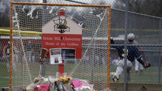 A lacrosse goal serves as a memorial for Seton Hill University's women's lacrosse coach Kristina Quigley on the school's  Greensburg, Pa. campus, Sunday, March 17, 2013. Coach Quigley and the tour bus driver were killed when a tour bus carrying three coaches and members of the Seton Hill women's lacrosse team crashed at about 9 a.m., Saturday morning on the Pennsylvania turnpike, spokeswoman Renee Colborn said. It's not clear what caused the crash, but state police were investigating, said Megan Silverstram of the Cumberland County public safety department. (AP Photo/Gene J. Puskar)