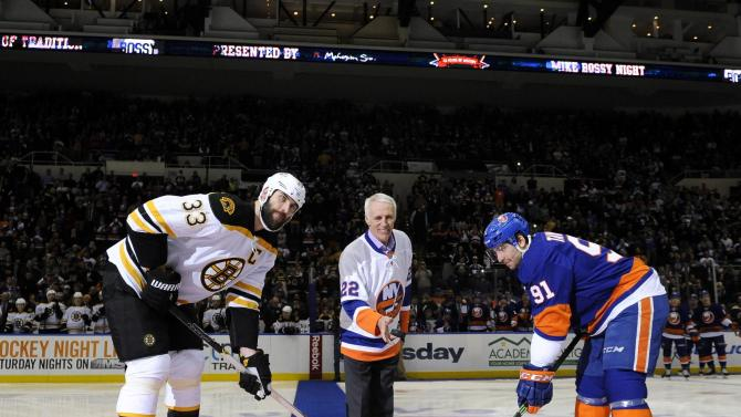 Hockey Hall of Famer and former New York Islander Mike Bossy drops a ceremonial first puck between Boston Bruins defenseman Zdeno Chara (33) and New York Islanders center John Tavares (91) before an NHL hockey game Thursday, Jan. 29, 2015, in Uniondale, N.Y. It was Mike Bossy tribute night at the Coliseum. (AP Photo/Kathy Kmonicek)