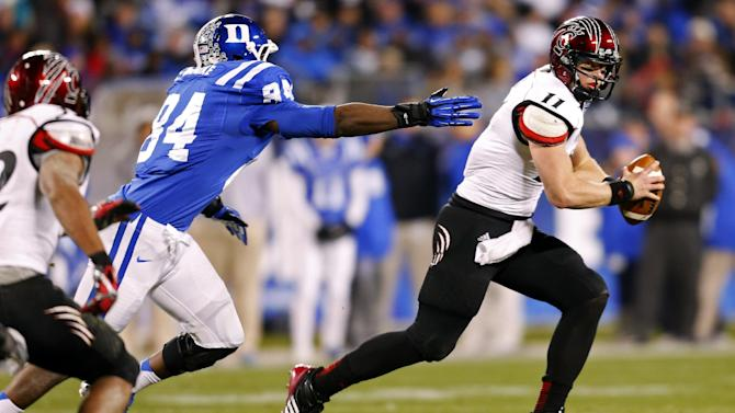 Cincinnati's Brendon Kay (11) scrambles as Duke's Kenny Anunike (84) pursues during the first half of the Belk Bowl NCAA college football game in Charlotte, N.C., Thursday, Dec. 27, 2012. (AP Photo/Chuck Burton)