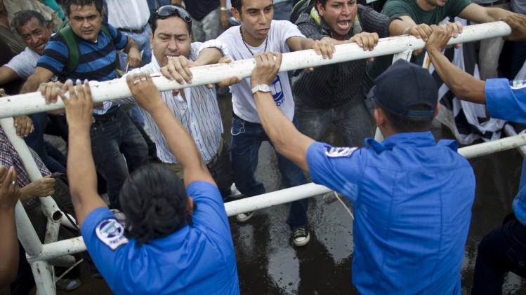 Anti-government protesters clash with police outside the National Assembly as the demonstrate against a canal project in Managua, Nicaragua, Thursday, June 13, 2013. A multi-billion dollar proposal to plow a massive rival to the Panama Canal across the middle of Nicaragua was approved by the National Assembly Thursday, capping a lightning-fast approval process that has provoked deep skepticism among shipping experts and concern among environmentalists. (AP Photo/Esteban Felix)