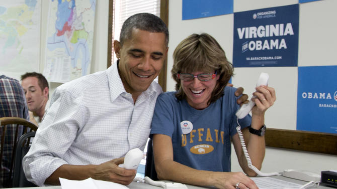 President Barack Obama makes phone calls to volunteers at an Obama campaign office with Suzanne Stern, right, Sunday, Oct. 14, 2012, in Williamsburg, Va. (AP Photo/Carolyn Kaster)