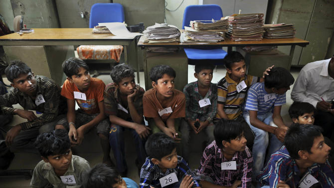 Young Indian bonded child laborers sit on the floor of the district magistrates office as they wait to be processed after being rescued during a raid by workers from Bachpan Bachao Andolan or Save the Childhood Movement, at a garment factory in New Delhi, India, Tuesday, June 12, 2012. Police raids on factories in the Indian capital revealed dozens of migrant kids hard at work Tuesday despite laws against child labor. Police rounded up 26 children from three textiles factories and a metal processing plant, but dozens more are believed to have escaped. Those captured had all come to New Delhi from the states of Bihar and Uttar Pradesh. (AP Photo/Kevin Frayer)