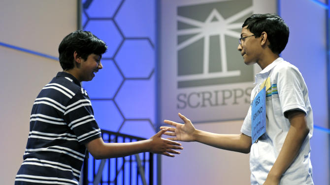 Scripps National Spelling Bee champion Arvind Mahankali, 13, of Bayside Hills, N.Y. extends his hand to second place finisher Pranav Sivakumar, 13, Tower Lakes, Ill., after Sivakumar incorrectly spelled his final word during the finals in Oxon Hill, Md., Thursday, May 30, 2013. (AP Photo/Cliff Owen)