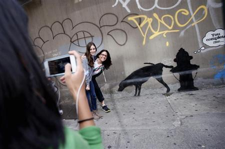 Two women have their picture taken next to new artwork by British graffiti artist Banksy on West 24th street in New York City