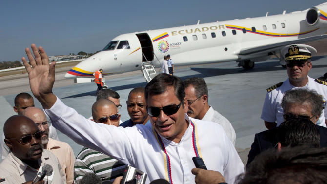 Ecuador's President Rafael Correa, center, greets reporters upon his arrival at the Jose Marti International airport in Havana, Cuba, Monday, Dec. 10, 2012. Correa traveled to Cuba to visit Venezuelan President Hugo Chavez, who arrived in Cuba early Monday for a third cancer operation. (AP Photo/Ramon Espinosa)
