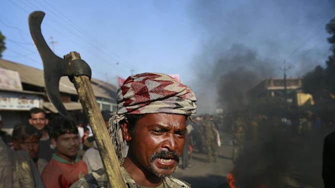An Indian tribal settler shout slogans as he blocks a road with other in protest against the attack by an indigenous separatist group on their villages, in Shamukjuli village in Sonitpur district of Indian eastern state of Assam, Wednesday, Dec. 24, 2014. Hundreds of survivors of a brutal rebel attack that killed at least 63 people in northeastern India sought shelter Wednesday in a church and school while security forces imposed a curfew in a bid to contain the latest bout of ethnic violence. (AP Photo/Anupam Nath)