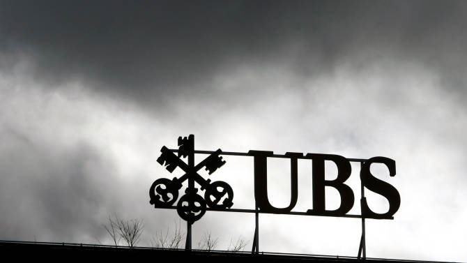 FILE - In this March 12, 2008 file photo dark clouds hang above the logo of the UBS in Zurich, Switzerland. Swiss banking giant UBS AG announced massive layoffs Tuesday, Oct. 30, 2012, along with huge losses in its third-quarter results, saying it aims to trim as many as 10,000 employees, or some 15 percent of its staff, to drastically shrink its ailing investment bank. (AP Photo/Keystone, Alessandro Della Bella, File)