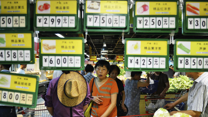 A shopper walks past price tags for vegetables at a supermarket in Hangzhou in eastern China's Zhejiang province Tuesday, July 9, 2013. China's inflation rose in June but was well below the government's target in a sign of weak demand amid an economic slowdown. (AP Photo) CHINA OUT