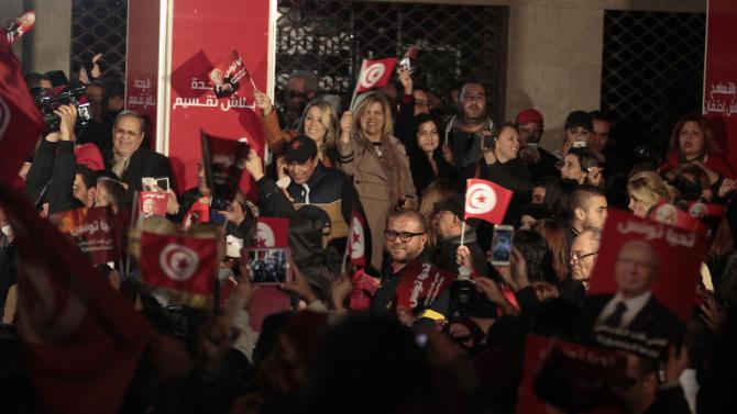 Supporters of the Nidaa Tounes (Call of Tunisia) secular party movement wave flags and shout slogans outside Nidaa Tounes in Tunis