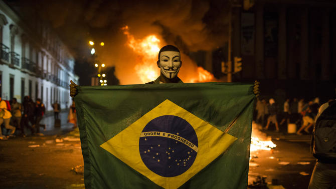 In this photo taken Monday, June 17, 2013, a demonstrator holds a Brazilian flag in front of a burning barricade during a protest in Rio de Janeiro in Rio de Janeiro, Brazil. President Dilma Rousseff has tried to placate the largely middle-class crowds by supporting their right to protest, and the Sao Paulo municipal government has rescinded the 10-cent hike in bus and subway fares that sparked the demonstrations in the first place. But as the protests grow even bigger, with two major marches called for Thursday, the Brazilian government seems at a loss over how to address the sweeping, urgent demands of its people. (AP Photo/Felipe Dana)