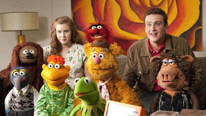 """In this film publicity image released by Disney, Amy Adams, left, and Jason Segel are shown with the muppet characters in a scene from """"The Muppets."""" (AP Photo/Disney Enterprises, Patrick Wymore)"""