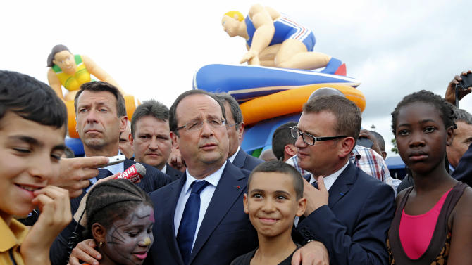FILE - In this Wednesday, July 31, 2013 file photo, French President Francois Hollande, center, poses with residents during his visit to 'Clichy Sand' in Clichy-sous-Bois, outside Paris. Two weeks after a spurt of rioting in a far-flung Paris suburb, Hollande is injecting a new dose of funds to help cure one of France's most persistent problems, the suburban housing projects with their volatile mix of joblessness, high immigration, crime and despair. (AP Photo/Jacques Brinon, Pool, File)