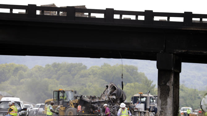 Emergency personnel work under an overpass blackened from a fire where a gasoline tanker truck exploded and burned after hitting the overpass on Interstate 65 near Franklin, Tenn., Friday Aug. 15, 2014. Officials said the driver of the truck, working for the Edwards Oil Co. of Lawrenceburg, was killed. (AP Photo/Mark Humphrey)