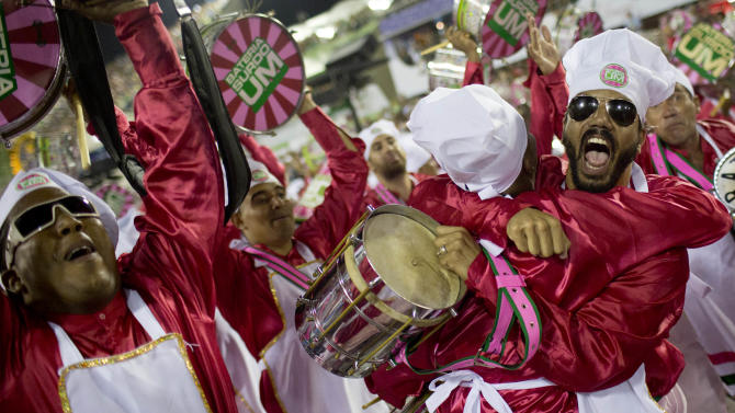 Performers from the Mangueira samba school embrace during carnival celebrations at the Sambadrome in Rio de Janeiro, Brazil, Monday, Feb. 11, 2013. (AP Photo/Felipe Dana)
