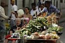 A man pushes his cart with vegetables and fruit for sale on a street in Havana