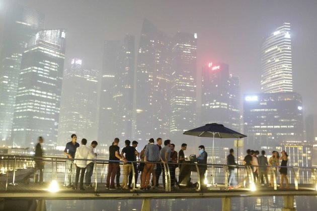 Partygoers line up to enter a nightclub at Marina Bay Sands, as haze shrouds the skyline of Singapore in the background