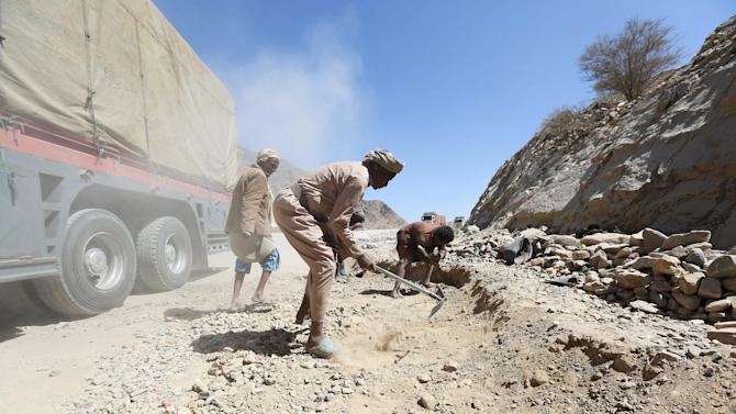 Drivers pave a road where cars and trucks are stuck as they take a detour from the main road due to fighting between pro-government forces and Houthi rebels, in Yemen's northern province of Marib