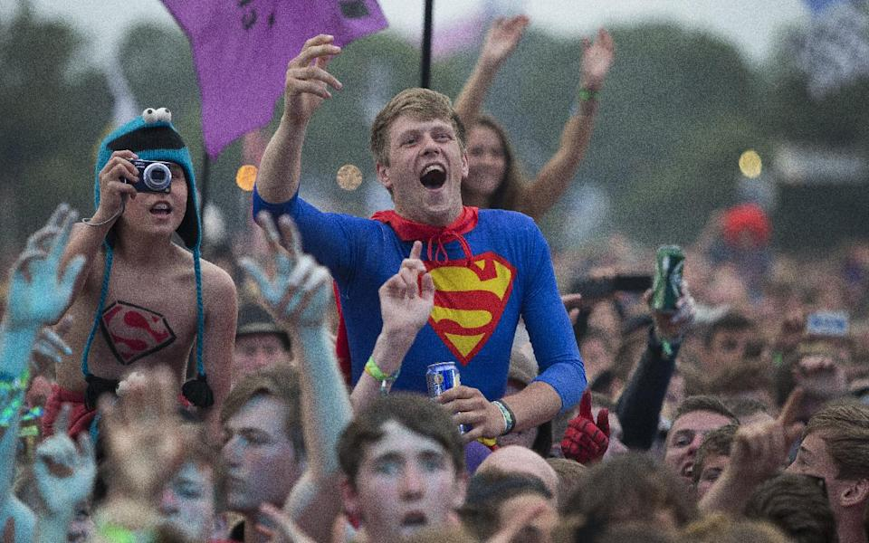 A man dressed as superman watches Dizzee Rascal perform on the Pyramid main stage at Glastonbury, England, Friday, June 28, 2013. Thousands of music fans have arrived for the festival to see headliners, Arctic Monkeys, Mumford and Sons and the Rolling Stones.(Photo by Joel Ryan/Invision/AP)