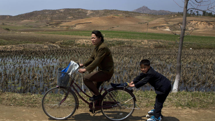 A North Korean boy on rollerblades is pulled by a woman on a bicycle on Wednesday, April 24, 2013, on a road south of Kaesong, North Korea and north of the demilitarized zone which separates the two Koreas. (AP Photo/David Guttenfelder)