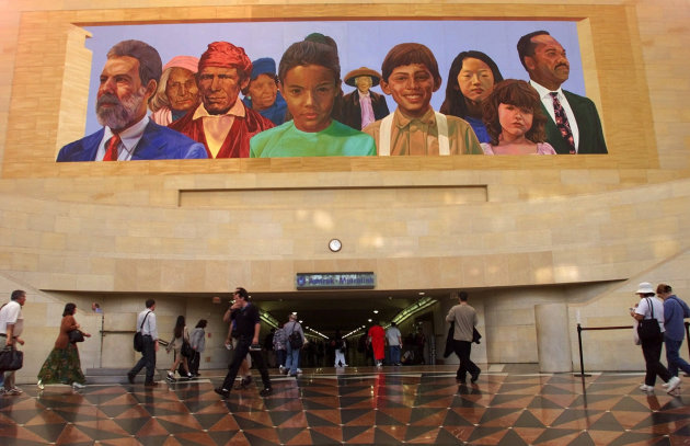"FILE - In this Aug. 30 2000, file photo, commuters walk into a tunnel at Los Angeles's  Amtrack-Metrolink Union Station under the mural ""City of Dreams/River of History"" by artist Richard Wyatt, showi"