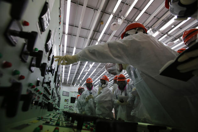 Members of the media and Tokyo Electric Power Co. (TEPCO) employees in protective suits and masks visit the central control room for the No. 1 and No. 2 reactors at the tsunami-crippled TEPCO's Fu