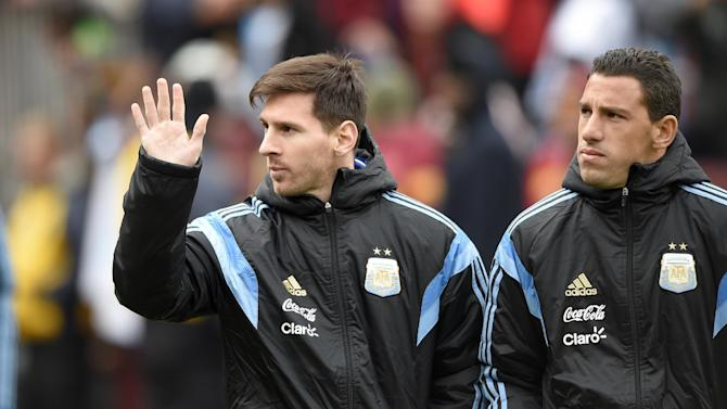 Argentina 's Lionel Messi, left, waves as he comes onto the field before an international friendly soccer game against El Salvador, Saturday, March 28, 2015, in Landover, Md. (AP Photo/Nick Wass)