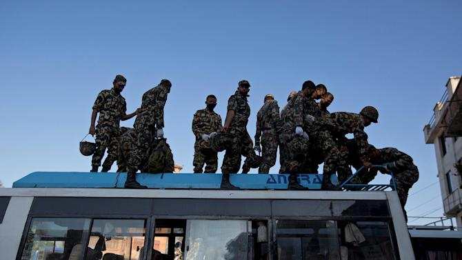 Nepal Army personnel get off from a bus as they arrive for a rescue mission in Sankhu, on the outskirts of Kathmandu