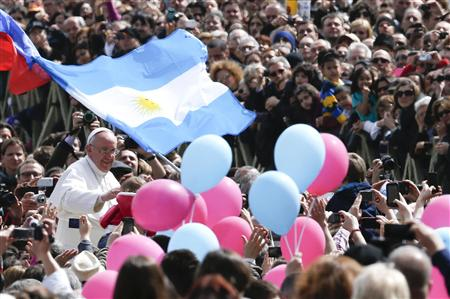 Pope Francis (L) waves near balloons and an Argentina flag as he leaves at the end of the Easter mass in St. Peter's Square at the Vatican March 31, 2013. REUTERS/Stefano Rellandini