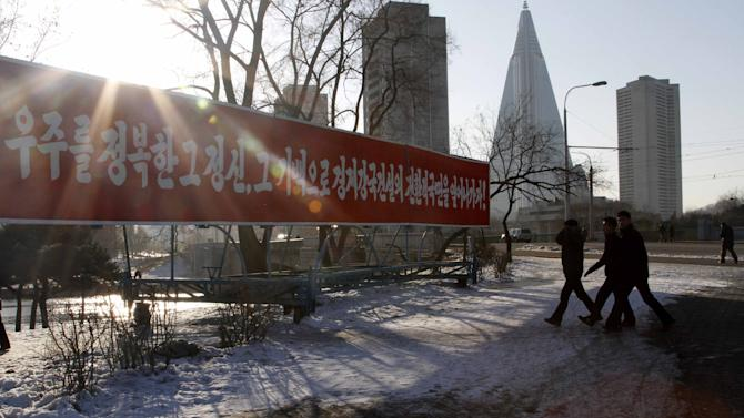 In this Jan. 24, 2013 photo, students walk toward Pothong River in Pothong District, Pyongyang, North Korea with the Ryugyong Hotel seen in the background, second right. The banner calls on the people to build a country into an economic power using the spirit of the scientists who sent a satellite into space. (AP Photo/Kim Kwang Hyon)