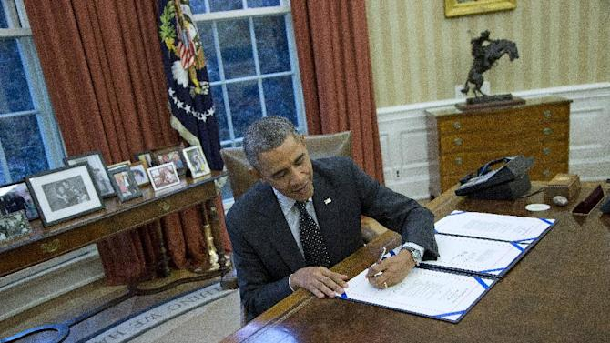 President Barack Obama signs H.R. 2747: the Streamlining Claims Processing for Federal Contractor Employees Act, Thursday, Nov. 21, 2013, in the Oval Office of the White House in Washington. (AP Photo/ Evan Vucci)