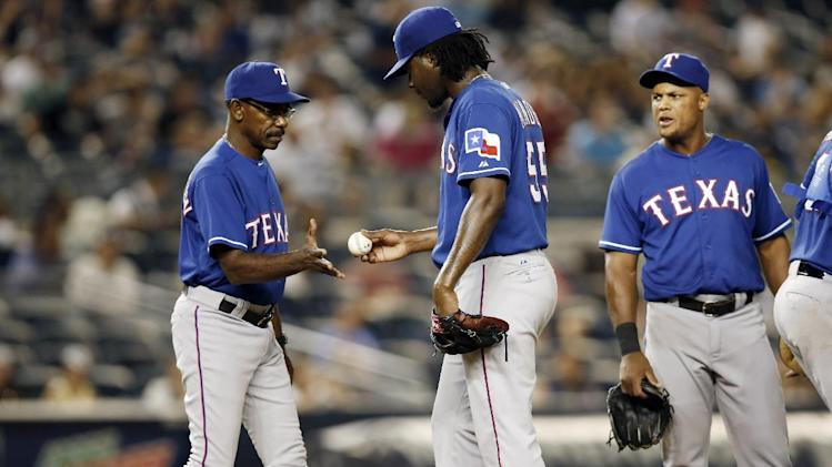 Texas Rangers manager Ron Washington, left, takes the ball from Rangers relief pitcher Roman Mendez (55) in the 11th inning of a baseball game against the New York Yankees at Yankee Stadium in New York, Tuesday, July 22, 2014. (AP Photo)