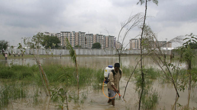 File - In this Sept. 8, 2010 file photo, a civic worker sprays pesticide to eliminate mosquito larvae to check the spread of malaria and dengue fever near the Commonwealth Games village, background, in New Delhi, India. India's preparations for the New Delhi games have become an international embarassment, with filthy athletes' housing, a collapsed pedestrian bridge, security worries and an outbreak of dengue fever. (AP Photo/File)