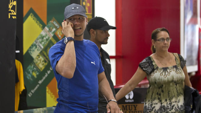 FILE- In this May 29, 2014, file photo, Yulieski Gourriel, player for the Cuban baseball team Industriales, speaks on his cell phone before catching his flight at the Jose Marti International Airport in Havana, Cuba. Gourriel left Cuba to join the DeNA BayStars of Yokohama, Japan. New rules let islanders play overseas as long as they fulfill their commitment to the domestic league and international competitions. Gourriel is scheduled to be back for Cuba's winter league in November. (AP Photo/Franklin Reyes, File)