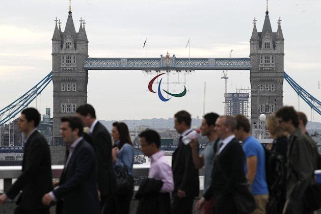 A Paralympic Games symbol hangs from Tower Bridge in London as City workers walk across London Bridge, Friday, Aug. 24, 2012. The London 2012 Paralympic Games starts on Wednesday, Aug. 29. (AP Photo/Sang Tan)