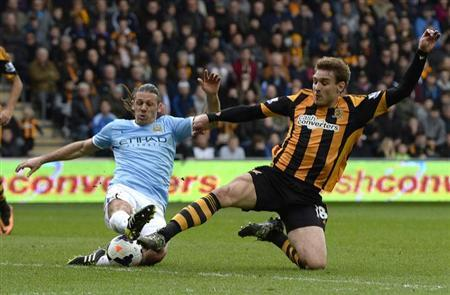 Manchester City's Martin Demachelis (L) challenges Hull City's Nikica Jelavic during their English Premier League soccer match at the KC stadium in Hull, northern England March 15, 2014. REUTE